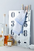 Clothes pegs decorated with tape on metal number stencil next to decorative vintage bottles