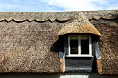 Traditional, English-style thatched roof with dormer window