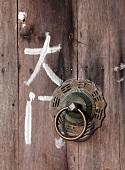 Chinese characters next to metal doorknocker on wooden door