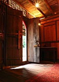 Traditional foyer with half-open front door in Oriental wooden house