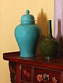 Turquoise china jar with lid next to vase on cabinet painted with floral motifs