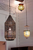 Various pendant lanterns, some with colourful lampshades, in corner of room