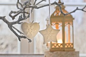 Christmas decorations hanging on tree and candlelit lantern