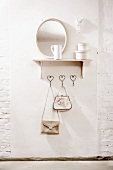 Coat hooks with handbags, shelf, mirror and antlers