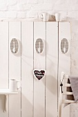 White wooden wall with hooks and gingerbread heart