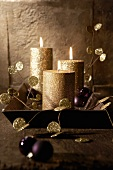 Gold candles and purple Christmas tree baubles on a tray