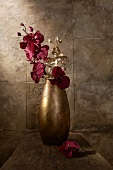 Goldbraune Vase mit lila und goldfarbenen Orchideen