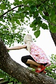 Blonde girl climbing a tree