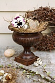 Still-life of straw nest with birds' eggs in amphora