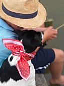 Angler sitzt mit Hund am Ufer