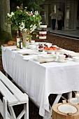 A summery garden table laid with a white cloth with a pebbled yard