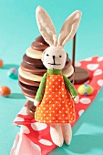 Plush rabbit toy in front of a chocolate Easter egg