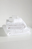 Stack of white towels on a white shelf