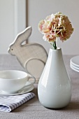 Easter atmosphere - carnation in ceramic vase on breakfast table