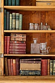 Antiquarian books and glass vessels in open wooden cabinet