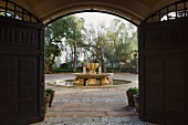 View of ornamental fountain in Mediterranean garden through open garden gate
