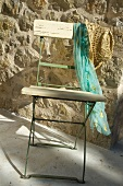 Simple folding chair with scarf and sunhat in front of stone wall