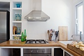 Modern kitchen counter with wooden work surface and stainless steel extractor hood