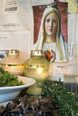 Mediterranean dishes and tea light holders in front of picture of the Madonna on wall