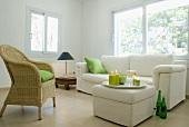 weiße Polstergarnitur und Korbsessel in minimalistischer Wohnraumecke