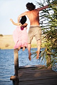 Couple jumping off dock into lake