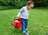 Toddler boy carrying watering can