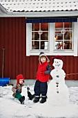 Boys making snowmen together