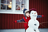 Boy playing with snowman outdoors