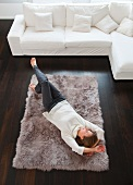 Smiling woman laying on rug