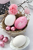 Easter arrangement with straw nest in dish, Easter eggs, chocolate eggs and paper flowers