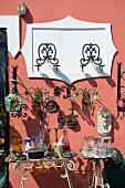 Flea market stall with antique sconces against brightly coloured, Mediterranean-style facade