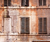 Weathered building facade with wooden shutters (Italy)