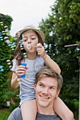 Girl sitting on father's shoulders blowing soap bubbles