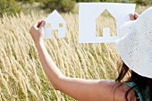 Woman holding up cut-out silhouette of house against meadow