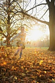 Girl playing with fallen autumn leaves in park