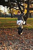 Girl swinging on tyre swing in park