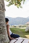 Junge sitzt auf Holzbank unter einem Baum