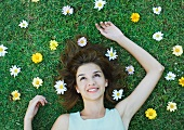 Woman lying on grass with flowers scattered around head