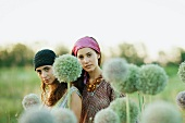 Young hippie women outdoors, allium flowers in blurred foreground
