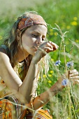Young woman picking wildflowers in field, cropped view, close-up