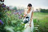 Young woman watering plants in garden with watering can, smiling at camera