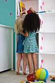Little girls reaching for book on shelf, rear view