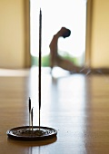Yoga class, woman doing cobra pose, focus on incense in foreground