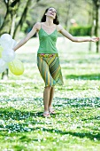 Young woman walking in meadow, holding balloons, arms out, smiling