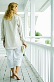 Woman walking on porch, carrying book, rear view