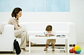 Young professional woman with briefcase sitting in waiting room while son colors