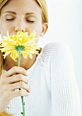 Woman smelling flower with eyes closed