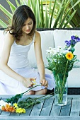 Young woman making flower arrangement outdoors