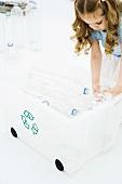 Little girl bending over, placing plastic bottles in recycling bin