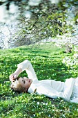 Teenage girl lying on the ground with eyes closed, holding flower, smiling